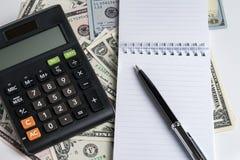 白皮书笔记本和笔,在美元钞票usi的计算器 免版税库存照片