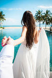白礼服藏品新郎的性感的新娘在豪华旅游胜地 浪漫游泳池的妇女主导的人 库存图片