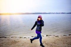 年轻白种人亭亭玉立的妇女生活方式画象沿海滩秋天跑 免版税库存图片