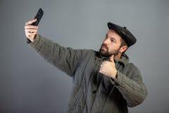 白种人人做selfie,演播室射击的35岁 想法-村庄居民和现代技术 免版税库存图片