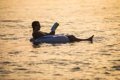 白种人人在日落在海洋水中读漂浮一本的书 夏天职业 库存照片