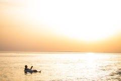 白种人人在日落在海洋水中读漂浮一本的书 夏天职业 免版税图库摄影