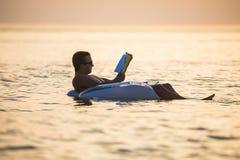 白种人人在日落在海洋水中读漂浮一本的书 夏天职业 图库摄影