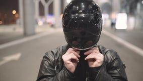 白种人人摩托车骑士头戴在夜街道上的一件盔甲 股票录像