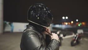 白种人人摩托车骑士头戴在夜街道上的一件盔甲 影视素材