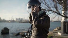 白种人人摩托车骑士头戴盔甲靠近港口冷的晴天 股票录像
