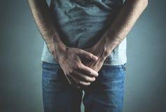 白种人人用拿着他的裤裆的手 炎症  库存图片