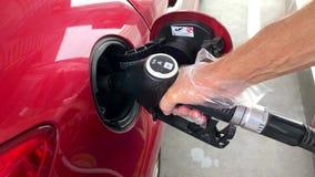 白种人人积土在加油站的红色汽车 影视素材