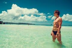 白种人人调查享受夏天海滩假期的距离 时刻旅行 释放重点 赤裸上身的适合运动男性身体 库存图片