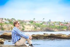 白种人人,坐由岩石峭壁的中间四十年代在水附近 免版税库存照片
