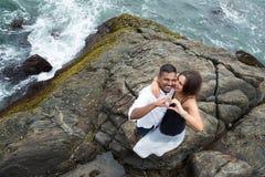 白种人做形状的女孩和她英俊的男朋友心脏标志由他们的手在海洋背景  库存图片