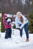 白种人做雪人的母亲和女儿,看照相机 库存照片