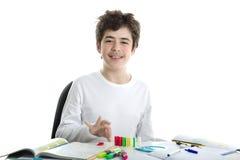 白种人光滑剥皮了使用与在家庭作业的多米诺的男孩 库存图片
