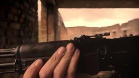 白种人军事男性和他的在被毁坏的砖瓦房的自动炮特写镜头射击在盔甲的,看 影视素材