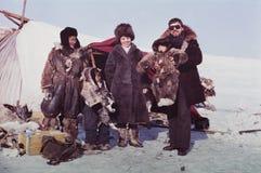 白种人参观土著人民的遥控站的男人和妇女 免版税库存图片