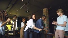 白种人和非裔美国人的青年人工友跳舞在获得乐趣和拍手的办公室聚会 现代 影视素材
