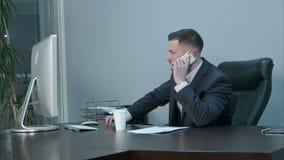 年轻白种人商人叫与智能手机和严重谈话在办公室 股票视频
