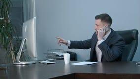 年轻白种人商人叫与智能手机和严重谈话在办公室 免版税库存图片