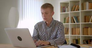 白种人商人画象镇静地与膝上型计算机轮一起使用对照相机和手表在书架背景 影视素材