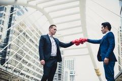 白种人商人穿戴黑色衣服和亚洲商人男服蓝色衣服与战斗由拳打的红色拳击手套 库存图片