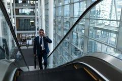 白种人商人谈话在手机,当提高在自动扶梯时 免版税库存图片