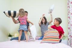 白种人四口之家有嬉戏的滑稽的枕头战 免版税图库摄影