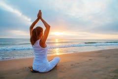 白种人在海滨的女子实践的瑜伽 免版税库存图片