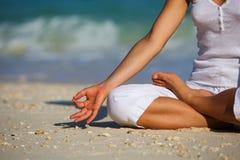 白种人在海滨的女子实践的瑜伽 免版税图库摄影