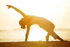 白种人在海滨的女子实践的瑜伽 免版税库存照片