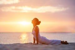 白种人在海滨的女子实践的瑜伽 库存照片