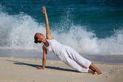 白种人在海滨的女子实践的瑜伽 图库摄影