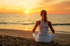 白种人在海滨的女子实践的瑜伽 库存图片