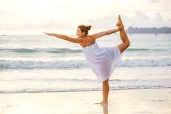 白种人在热带海洋海滨的女子实践的瑜伽  免版税库存照片