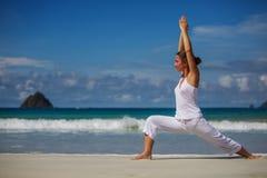 白种人在热带海洋海滨的女子实践的瑜伽  图库摄影