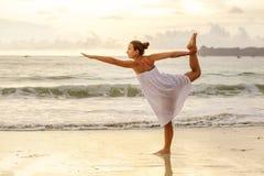 白种人在热带海洋海滨的女子实践的瑜伽  库存图片