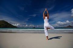 白种人在热带海洋海滨的女子实践的瑜伽  免版税图库摄影