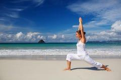 白种人在热带海洋海滨的女子实践的瑜伽  免版税库存图片