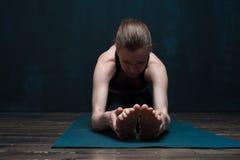 年轻白种人在蓝色席子的女子实践的瑜伽 库存图片