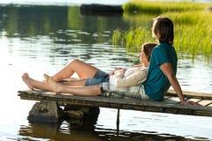 白种人夫妇lounging在码头日落 免版税库存照片