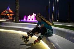 白种人女孩享受滑旱冰在有光的夜城市在bokeh 免版税库存图片