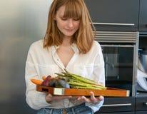 白种人女孩在一个现代厨房,准备有些菜 免版税库存照片