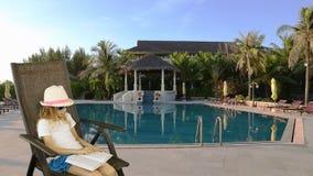 年轻白种人女孩坐扶手椅子和阅读书 游泳池和棕榈树在背景 有同样夹子 影视素材