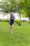 白种人女孩奔跑在与被弄乱的头发的夏天 免版税库存照片