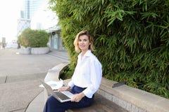 白种人女实业家与膝上型计算机和纸一起使用在露天在绿色植物附近 免版税图库摄影