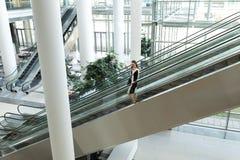 白种人女性执行委员谈话在手机,当移动下来在现代自动扶梯时 图库摄影