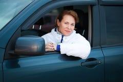 年轻白种人妇女作为在一辆大汽车的一个司机 免版税库存图片