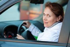 年轻白种人妇女作为在汽车的一个司机 库存图片