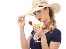 白种人妇女佩带的泳装,帽子和举行饮料 图库摄影