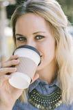 白种人妇女啜饮的咖啡,当微笑时 免版税库存图片