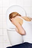 年轻白种人妇女在卫生间里呕吐。 免版税库存图片